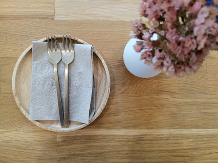 Tissue with two fork brass on brown rustic wooden table  top view from above with copy space