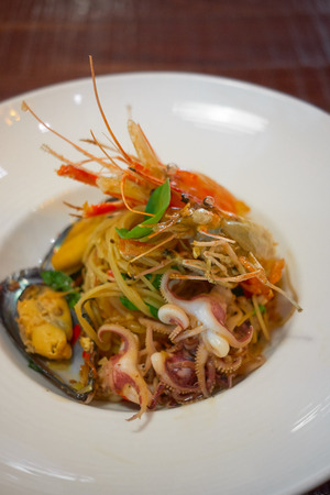 Spicy Seafood Spaghetti stir fried (Pad Cha) rolled in the fork on white dish of luxury restaurant, Thai Signature Food Stok Fotoğraf