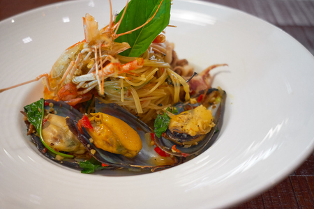 Spicy Seafood Spaghetti stir fried (Pad Cha) rolled in the fork on white dish of luxury restaurant, Thai Signature Food 版權商用圖片