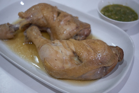 boiled chicken leg in fish sauce brown soup white plate