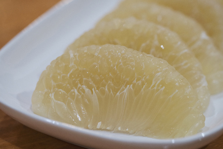 Pomelo is a natural citrus fruit on white plate, native to South and Southeast Asia Stok Fotoğraf
