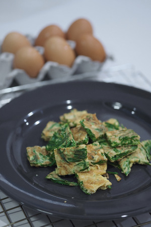 Warm Fried Eggs with Climbing Wattle in Black Dish thai food