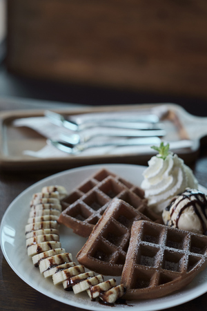 Homemade Belgian waffles with with bananas and ice cream.