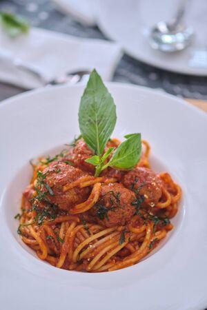 Meatballs served over italian spaghetti pasta with tomato sauce in restaurant