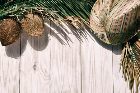 Tropical palm tree leaf on white wooden background  with sun hat and coconuts . Concept for vacation or summer.