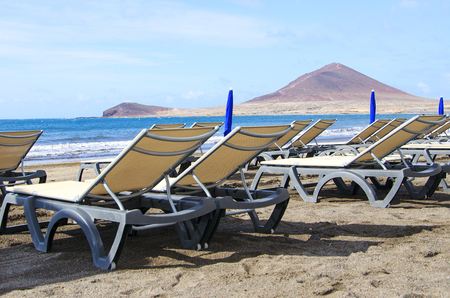 median: Two sunbeds on a beautiful beach of Medano, Tenerife, Canary Islands. Concept for vacations or tourism