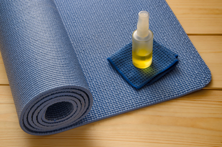 Blue yoga mat with cleaner on wooden background Archivio Fotografico