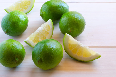 Fresh organic limes  with water drops on wooden background Stock Photo