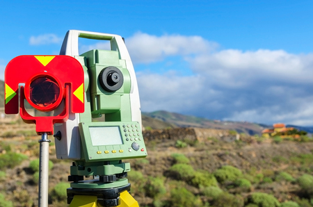 Modern surveyor equipment, theodolite with prism used in surveying and building construction for precise measurement. Total station outdoor at construction site. Copy space. Stock Photo