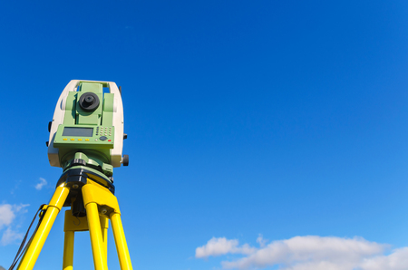 Modern surveyor equipment, theodolite or tacheometer  used in surveying and building construction for precise measurement. Total station outdoor against blue sky. Copy space.