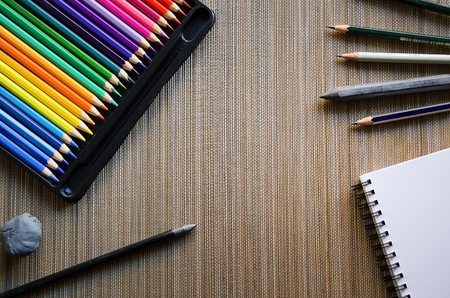 Colored pencils, crayon, sketch pad and Eraser on grey background with copyspace