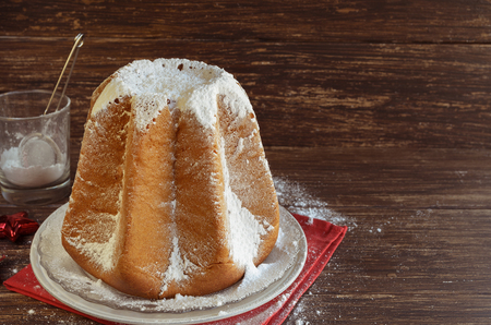 Delicious Christmas cake Pandoro with vanilla scented icing sugar traditiolly consumed at Christmas times in Italy. Italian sweet yeast bread with christmas decoration on wooden.Copy space