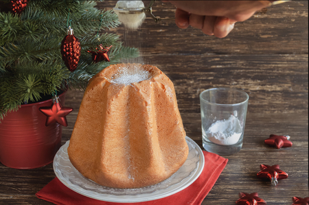Delicious Christmas cake Pandoro with  vanilla scente icing sugar traditiolly consumed at Christmas times in Italy. Italian sweet yeast bread with christmas decoration on wooden background.