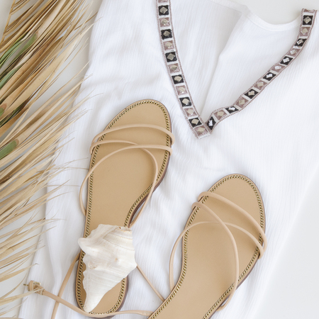 Summer vacation background. Flat lay beach accessories, Top view of green palm leaf and ocean shell,  white tunic  and sandals. Concept for summer times and travel.  Stock Photo