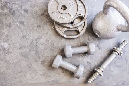 Weight plates for barbell, grey dumbbells, kettlebell and water bottle in cement floor in gym.