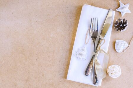Beautiful decoration for Christmas or New Year celebration. Festive dinner table settings, white napkin with silver cutlery,  christmas tree and cones on craft background. Copy space