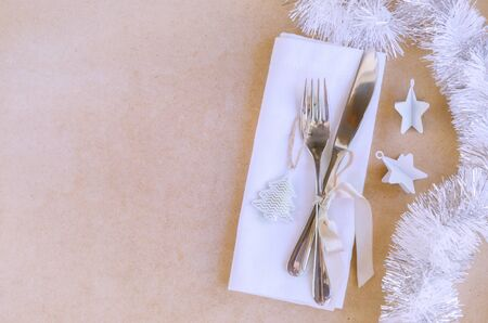 Beautiful decoration for Christmas or New Year celebration. Festive dinner table settings, white napkin with silver cutlery  and gold bow, christmas tree, cones, tinsel on craft background.Copy space