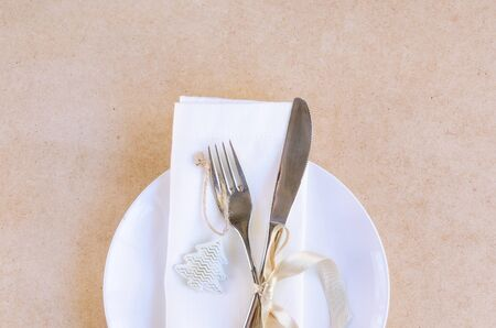 Beautiful decoration for festive dinner in beige white tone . Christmas table settings, white napkin with silver cutlery and christmas tree toy on craft background. Copy space
