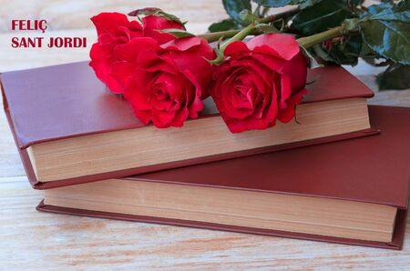 Old books and red rose, traditional gift for Sant Jordi, the Saint Georges Day. Catalunya's version of Valentine's day.Phrase Happy Saint Georges in catalan