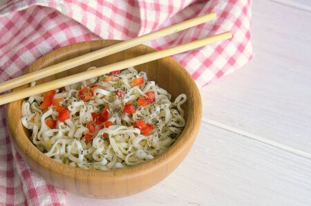 Instant noodles with on wooden bowl and chopsticks on white background with copy space. Typical Asian street food concept.