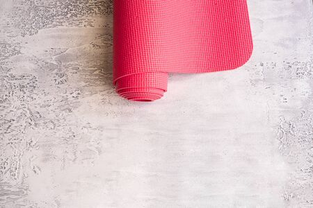 Yoga mat on white concrete background. Concept for doing Hatha yoga. Copy space. Stock Photo