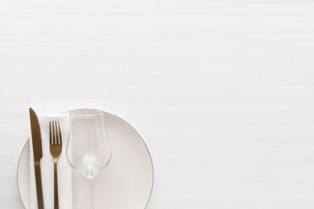Basic Table set , white plate,linen napkin; gold cutlery and glass on the table.Copy space