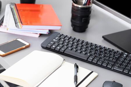 Open notepad with pen on the table with keyboard ,computer mouse and smarthphone .Remote work and earning online Foto de archivo