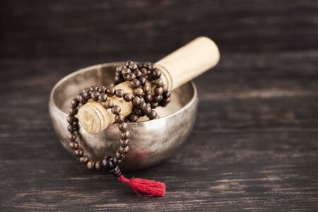 Classic Tibetan singing bowl and wiinem mala beads on wooden background with copy space.Toned image