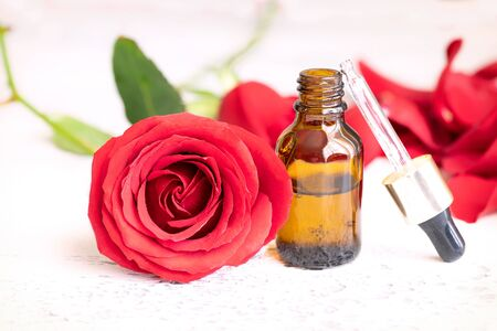 Essential rose oil in glass bottle and fresh rose flower on light background with copy space. Concept alternative health care for wellness and Aromatherapy. Stock Photo