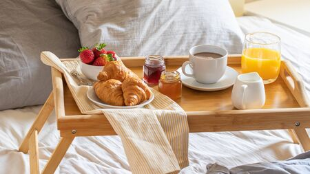 Breakfast on the bed inside a bedroom. Cup of coffee, orange juice, croissant, jam and strawberry on wooden try. Good morning concept. Stock Photo