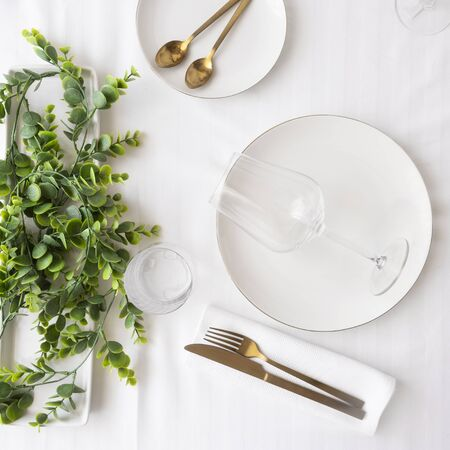 Top view of tableware with linen napkins, gold cutlery and white porcelain plates. Table settings background