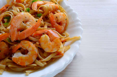 Close up of pasta with prawn on wooden background with copyspace