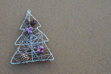 Christmas tree decoration on sand in the beach. Concept for tropical holidays. Copy space.