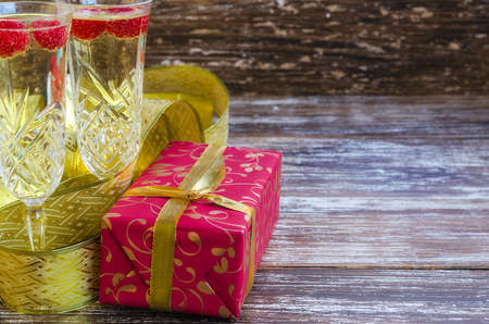 Close up of two champagne glasses with raspberry and red gift box with golden ribbon. Celebration background with copy space. Stock fotó
