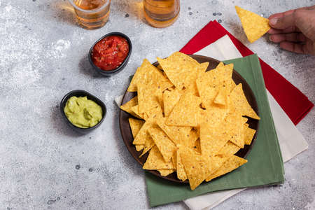 The most famous Mexican snack, nachos with guacamole, red chilli sauce and beer on cement background. Top view.