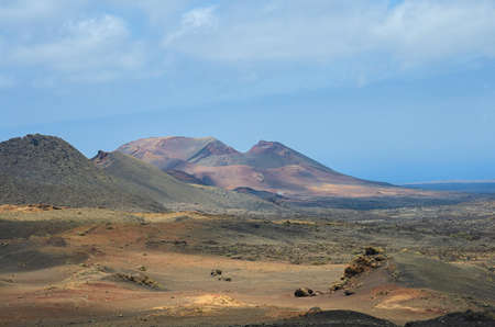 View of volcanic crater in Valle del Silencio, Valley of Silence in Timanfaya National Park in Lanzarote, Canary Islands, Spain. The spectacular volcanic landscape background.