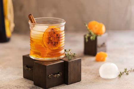 Whiskey sour cocktail with tangerine slices and ice cubes decorated with cinnamon and thyme. Alcohol drink background.