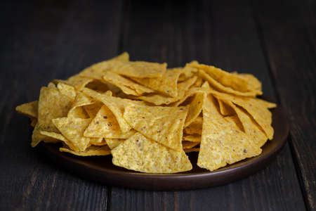 The most famous Mexican snack, nachos made with corn tortilla chips or totopos on wooden background.