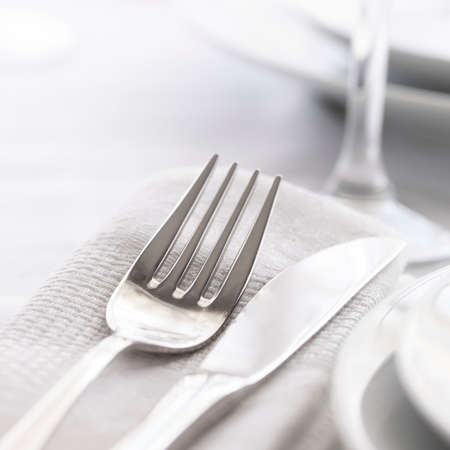 Close up of Silver fork and knife withnapkin and glass. Restaurant dinning concept.