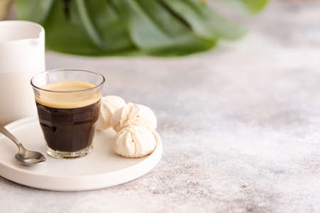 Cup on black coffee with green palm leaf for lifestyle and blogger concept. Work in paradise concept. Copy space.