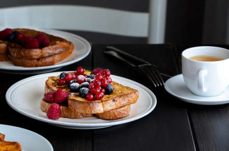 Fresh french toasts with fruit and cup of coffee on wooden table in restaurant. Good breakfast background. Archivio Fotografico