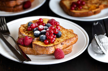 Traditional French toast with berries: blueberries, currant, raspberries and icing sugar for perfect sweet breakfast. Delicious dessert background. Archivio Fotografico
