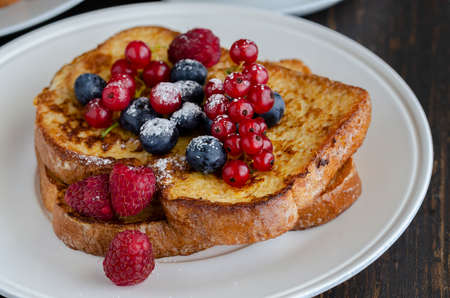 Close up of French toasts with fruit on the plate. Restaurant menu image. Archivio Fotografico