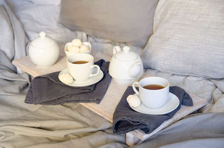 Breakfast In Bed: teapot, two cup of tea and swetts meringue on wooden tray. Good morning scenery background. Scandinavian style.