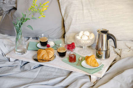 Romantic Breakfast or brunch for two in bed. Coffee maker and coffee glasses, croissants, jam, berries, meringue and flowers on wood tray. Romantic good morning scenery Archivio Fotografico