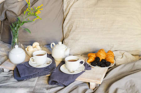 Breakfast In Bed: teapot, two cup of tea, croissants and meringue on wooden tray. Good morning scenery background. Scandinavian style. Archivio Fotografico