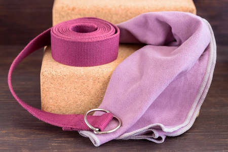 Close up of yoga props, cork blocks, violet yoga strap and lilac towel for doing yoga on wooden floor. Yoga props background.