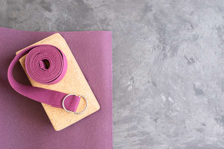 Open yoga mat with cork block and yoga belt. Yoga practice props background. Copy space.