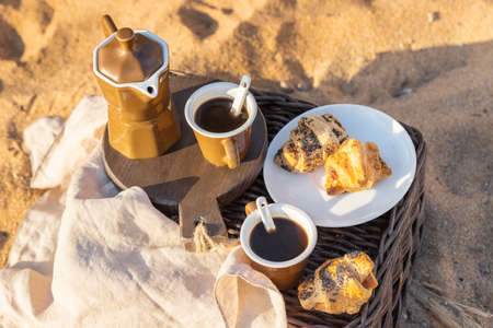 Breakfast on the beach for two. Coffee maker with cups and French croissants. Romantic date background.Picnic at sunrise.