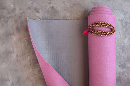 Yoga mat and classic mala beads, essential things for yoga practice and meditation.Copy space